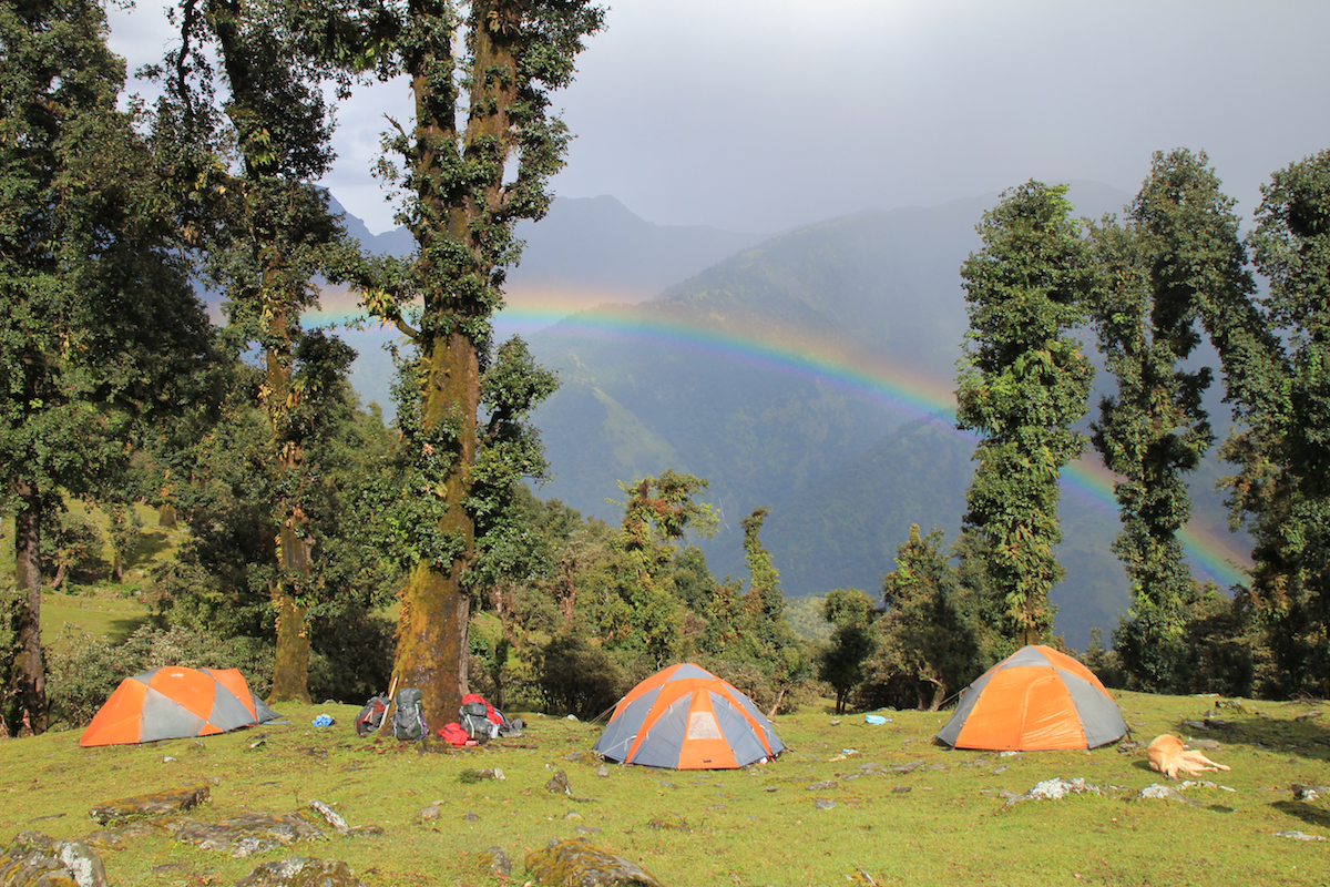 three NOLS tents in the Himalaya with a rainbow overhead