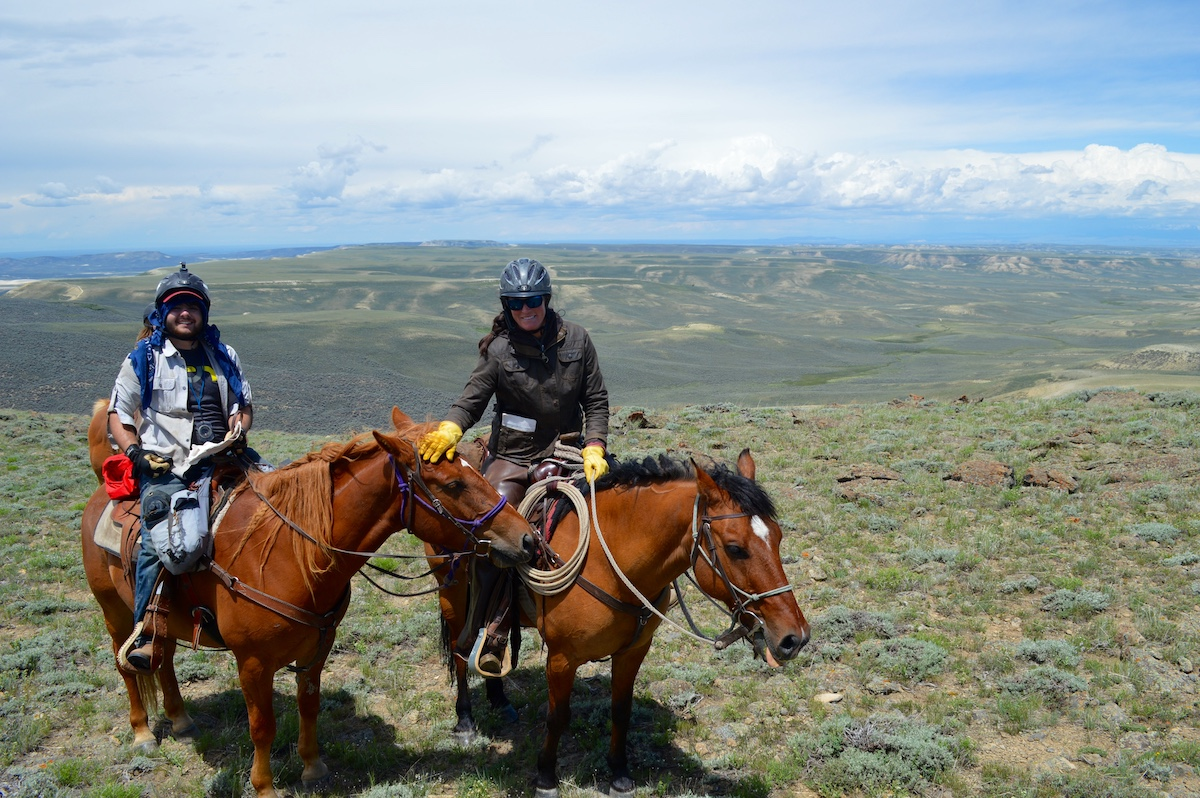 two NOLS participants on horseback smile at the camera