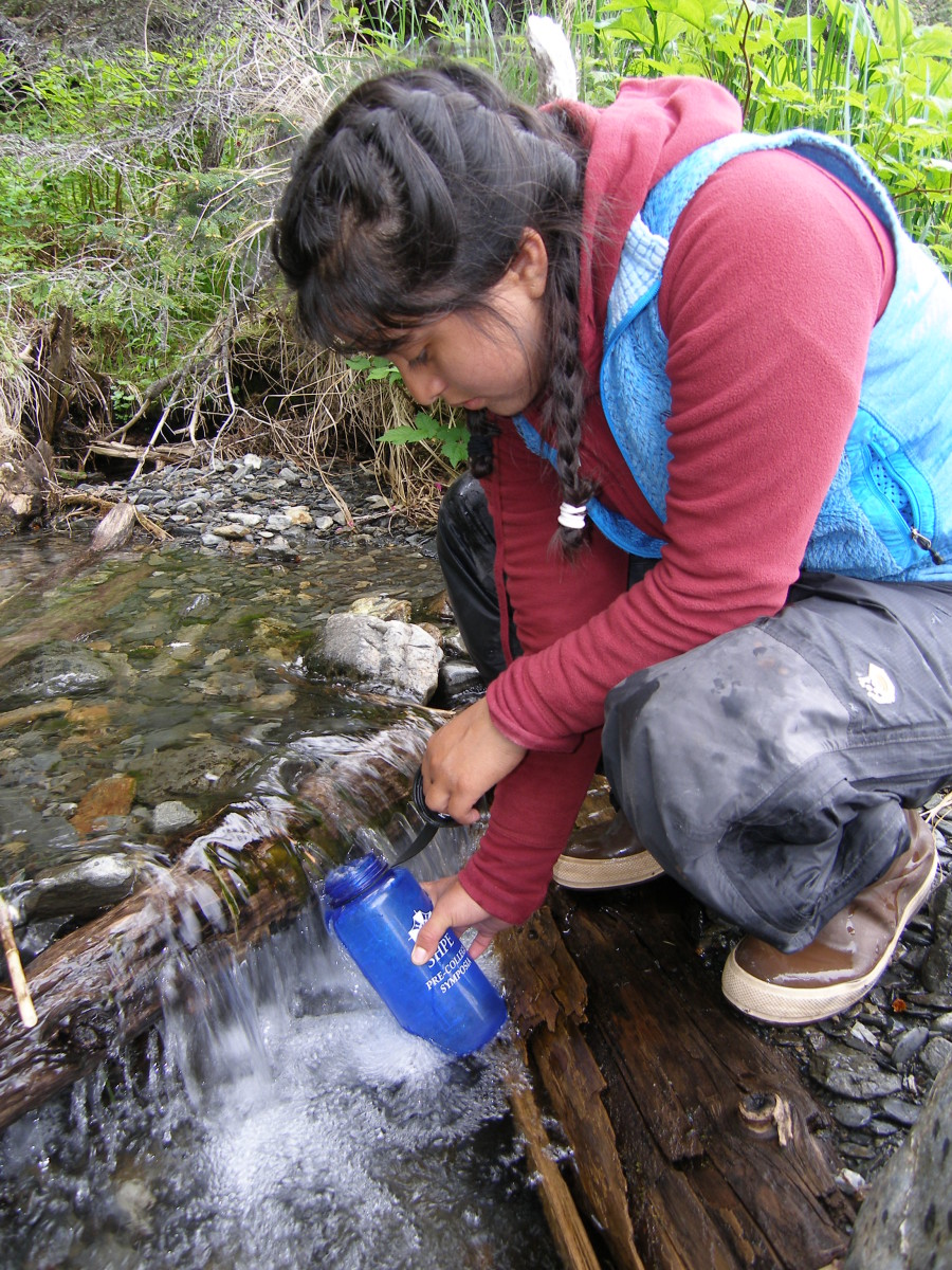 Hiker filling up water bottle from a stream