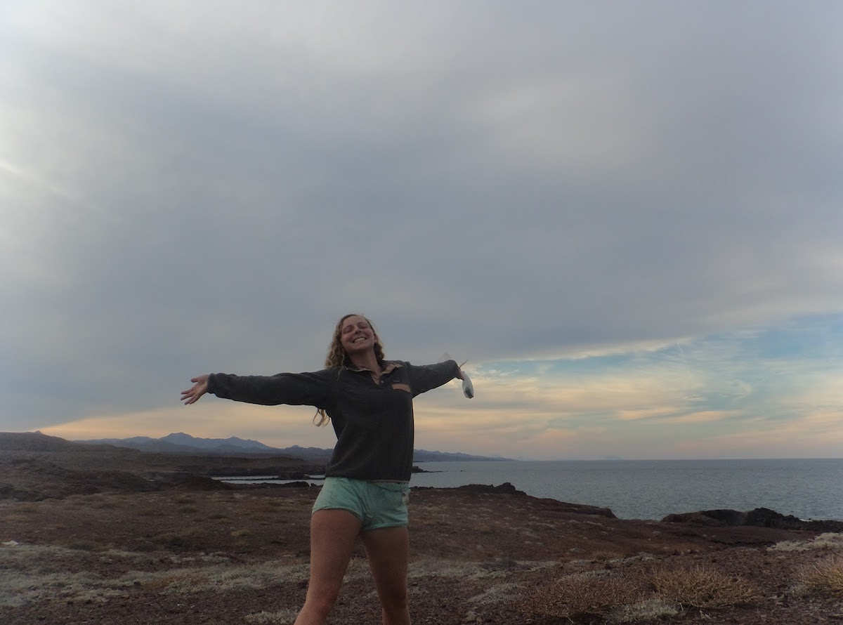 smiling NOLS student with arms outstretched on Baja coast
