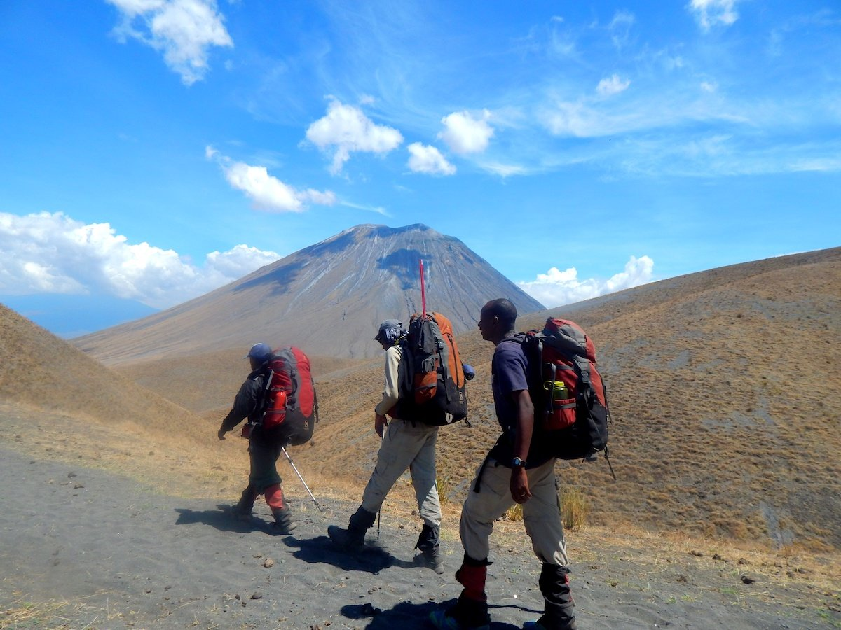 3 course participants trek with mountain in the background