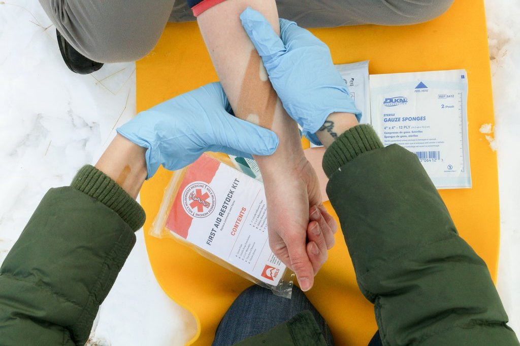 close-up of gloved hands applying a bandage during a NOLS scenario