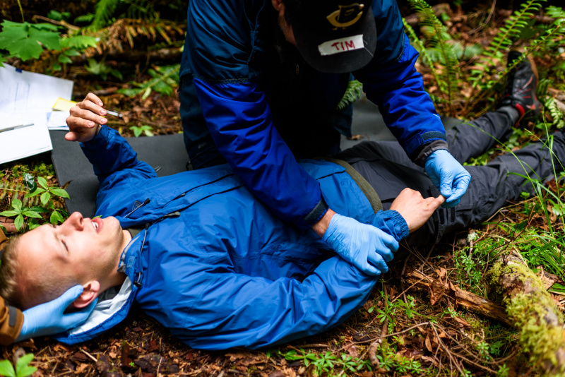NOLS student practices patient assessment by checking patient's hand during a scenario on their course