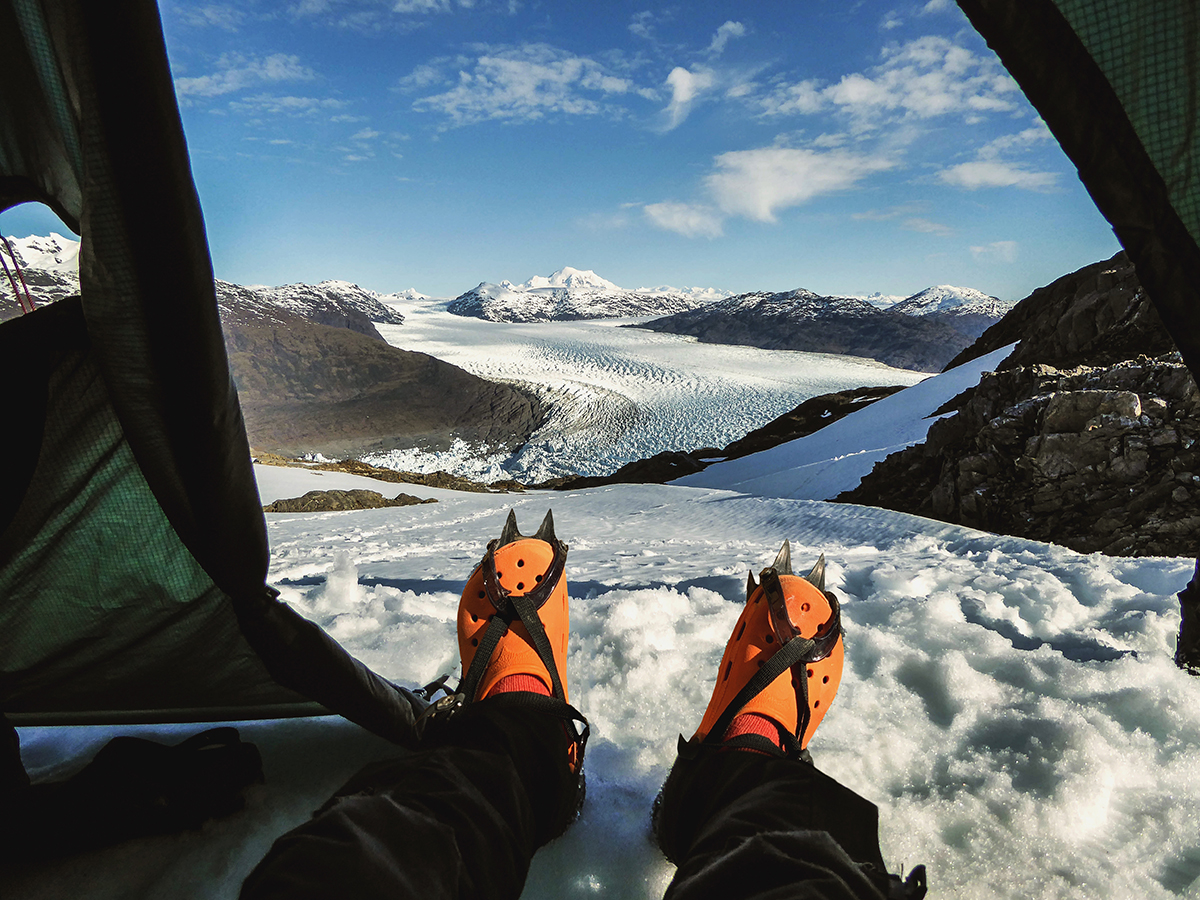 Spoof NOLS gear: camp shoes with crampons with glacier background