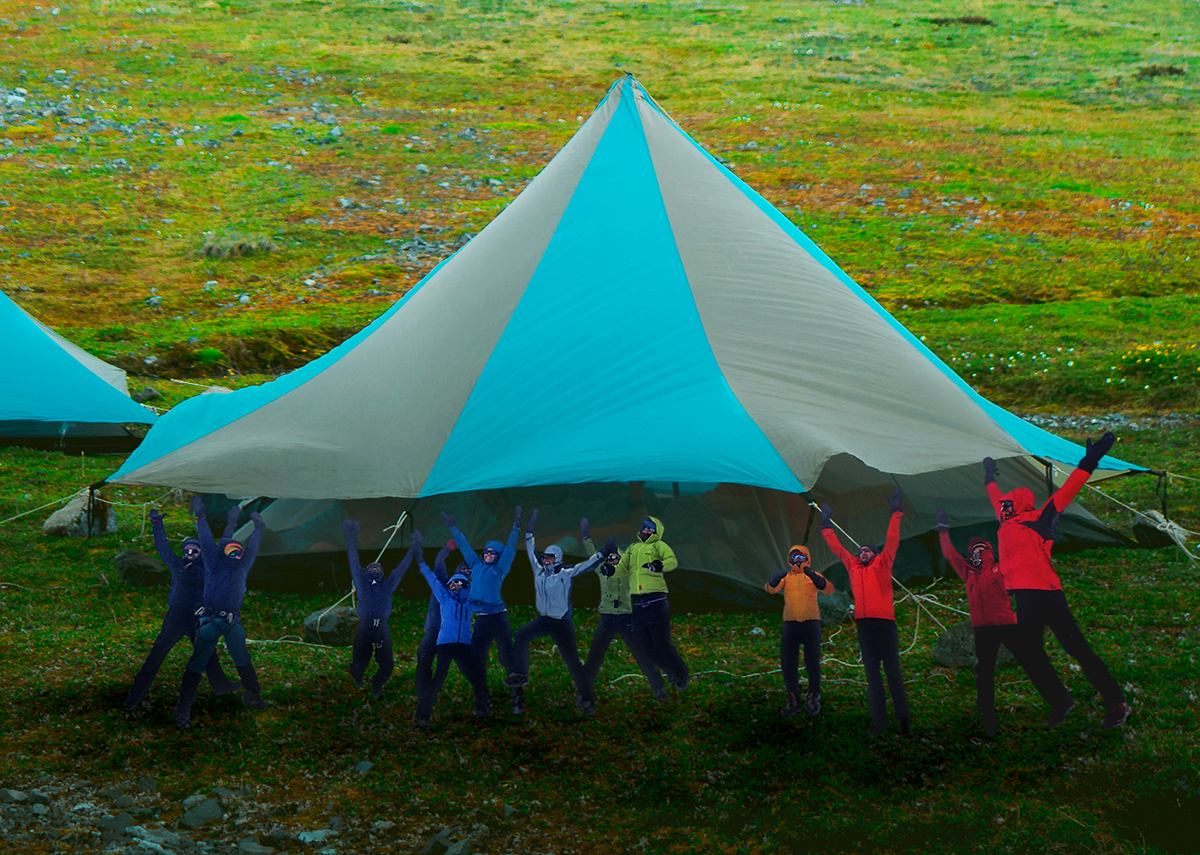 People in colorful jackets jump into the air with raised arms in front of a giant blue and tan tent