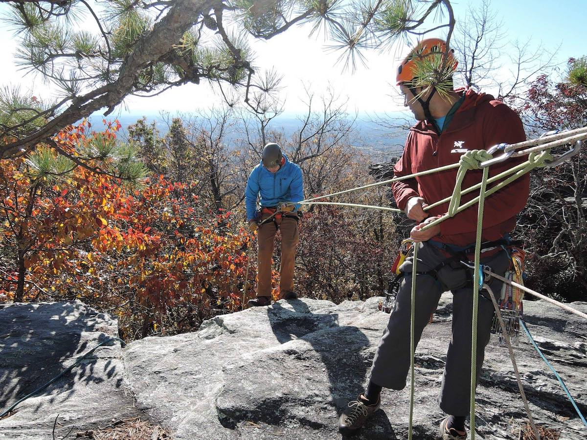 rock climbers connected by a harness at the top of a climb with fall leaves behind and pine branch overhanging