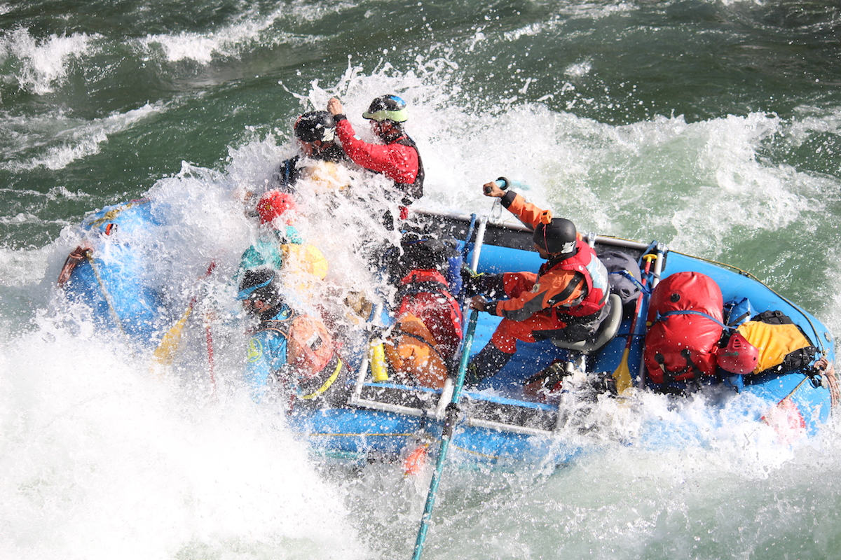 Group of people raft through a rapid