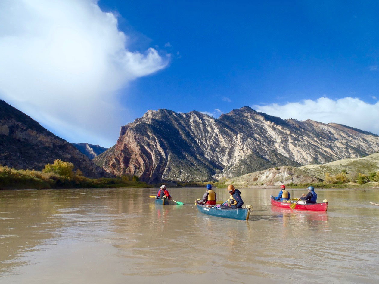 Students canoe on a river in the desert