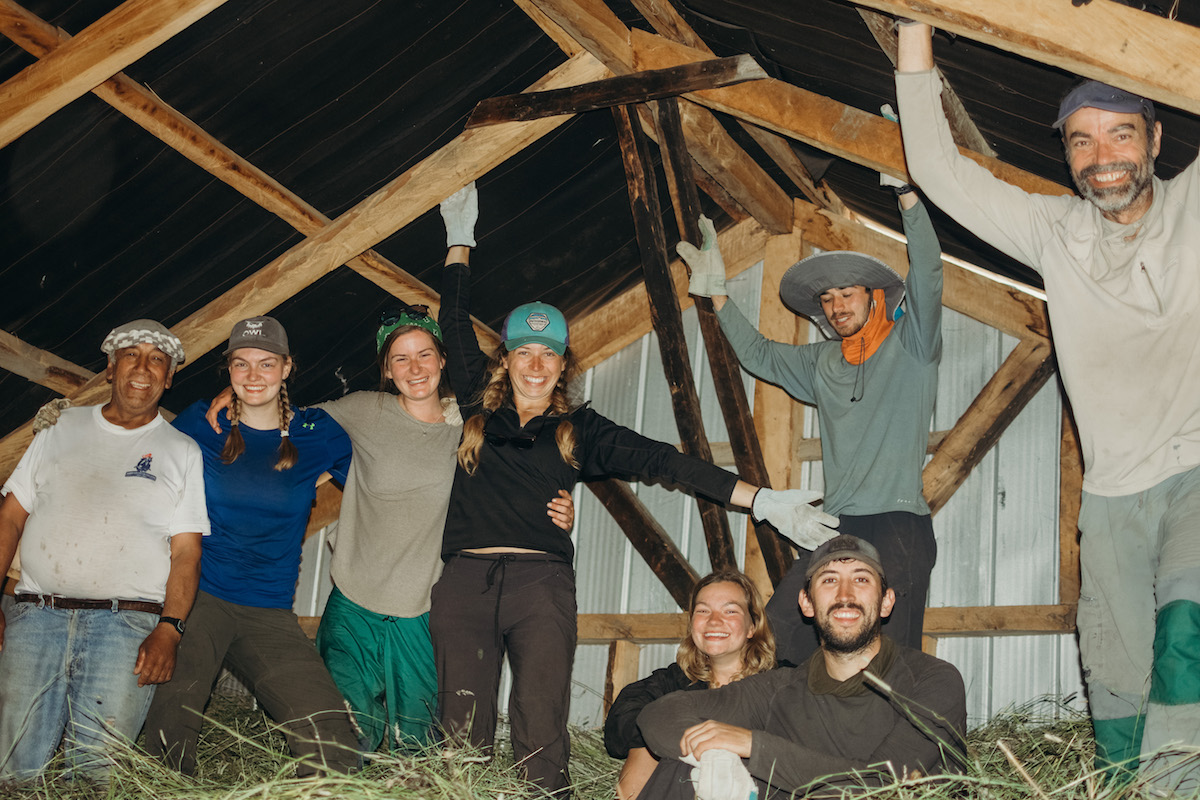 eight smiling people standing in hay in a barn in Patagonia