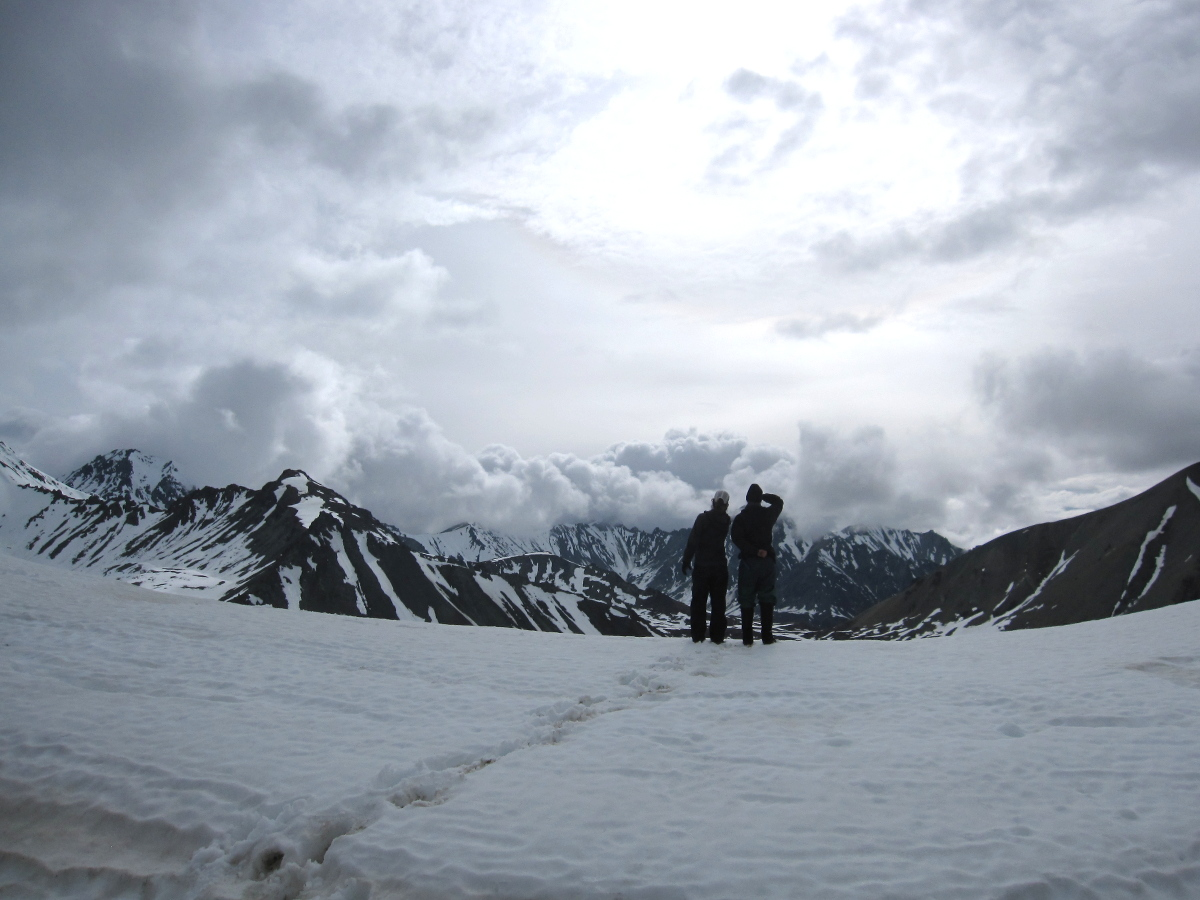 two silhouetted figures stand on a snowfield in Alaska, looking out toward mountains topped with clouds