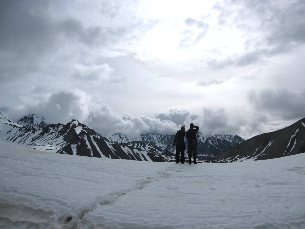 Two people look at the view from a snow slope in Alaska mountains