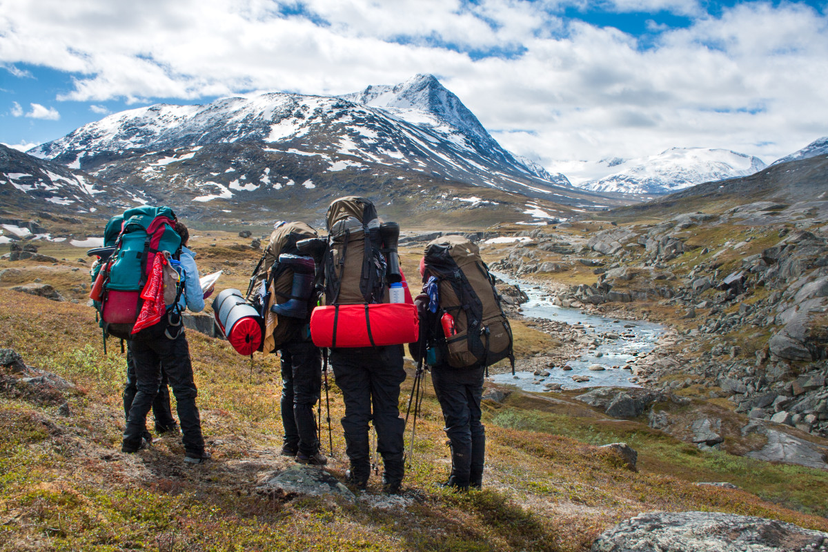 Backpacking group overlooking river valley in Scandinavia