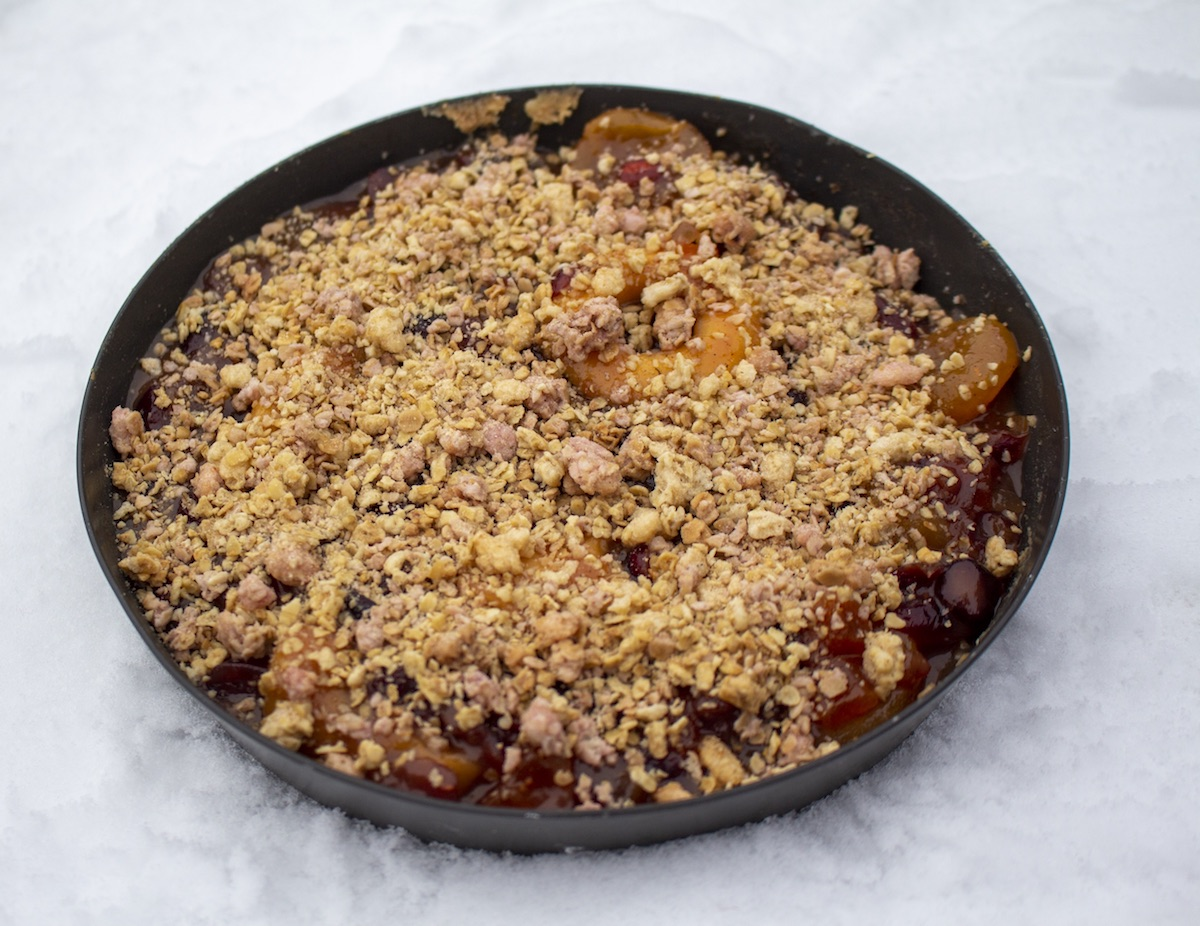 backcountry pie with garnished top sits in a frying pan in the snow