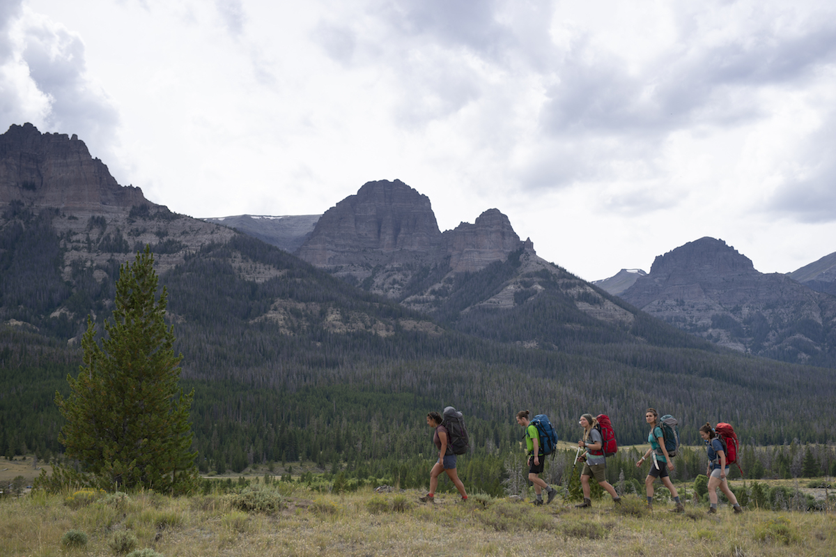 four backpackers hiking past pines and rocky peaks under cloudy sky