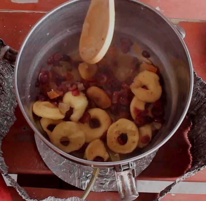 wooden spoon stirs re-hydrated dried fruit to make pie filling