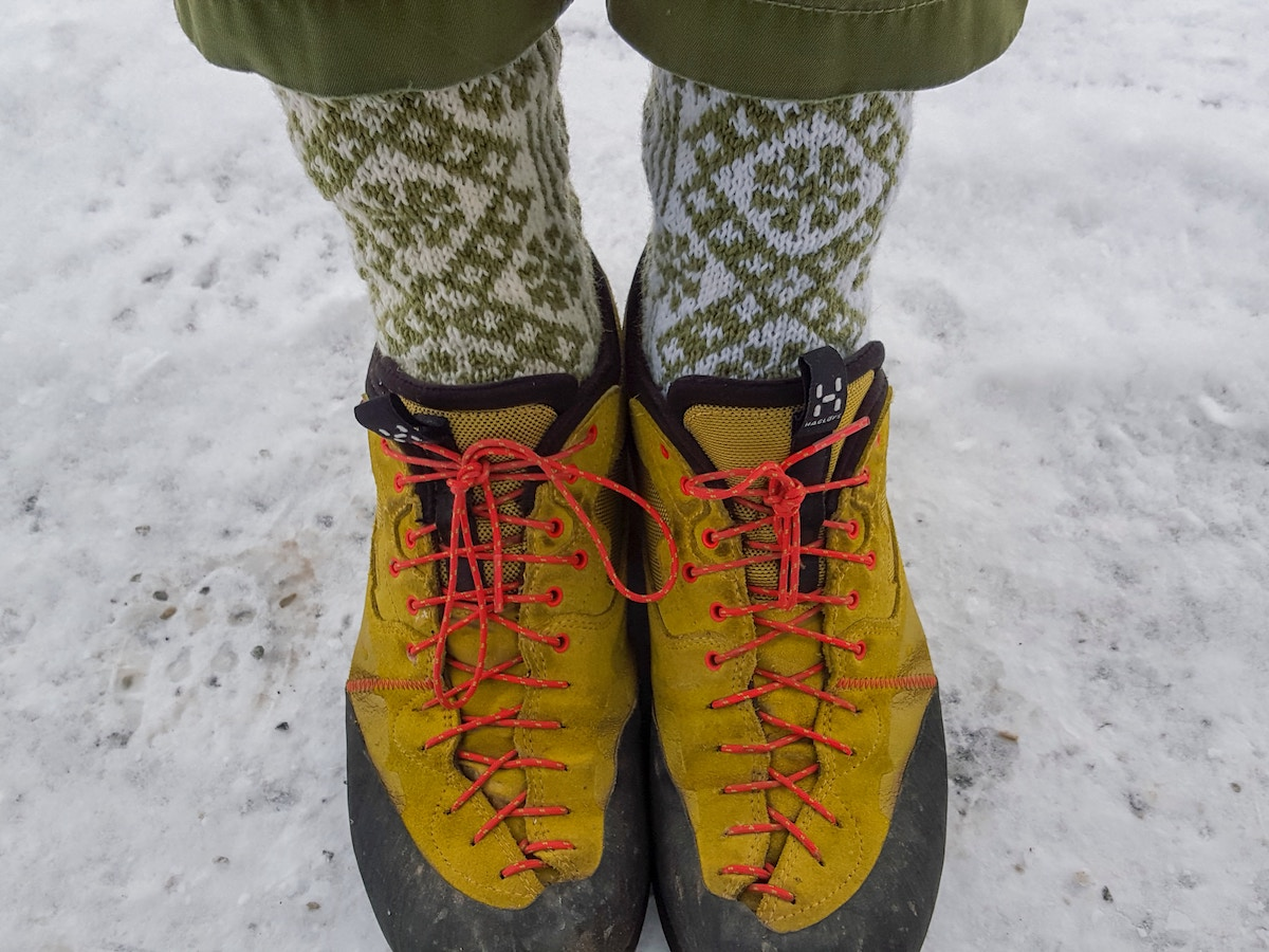 feet in yellow shoes with neon laces and green and white socks with snowflake pattern