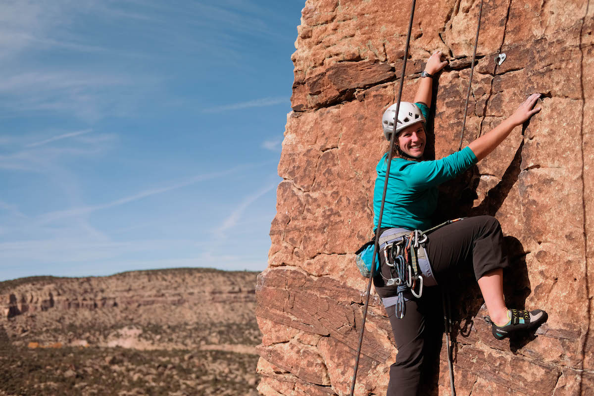 smiling NOLS student climbing on reddish rock