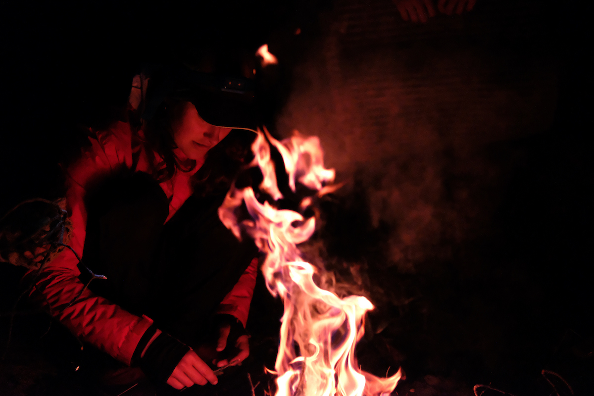 person wearing baseball cap tends campfire at night