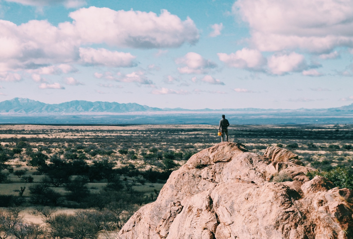 NOLS student stands on rocky outcrop at Cochise Stronghold and looks out at desert landscape
