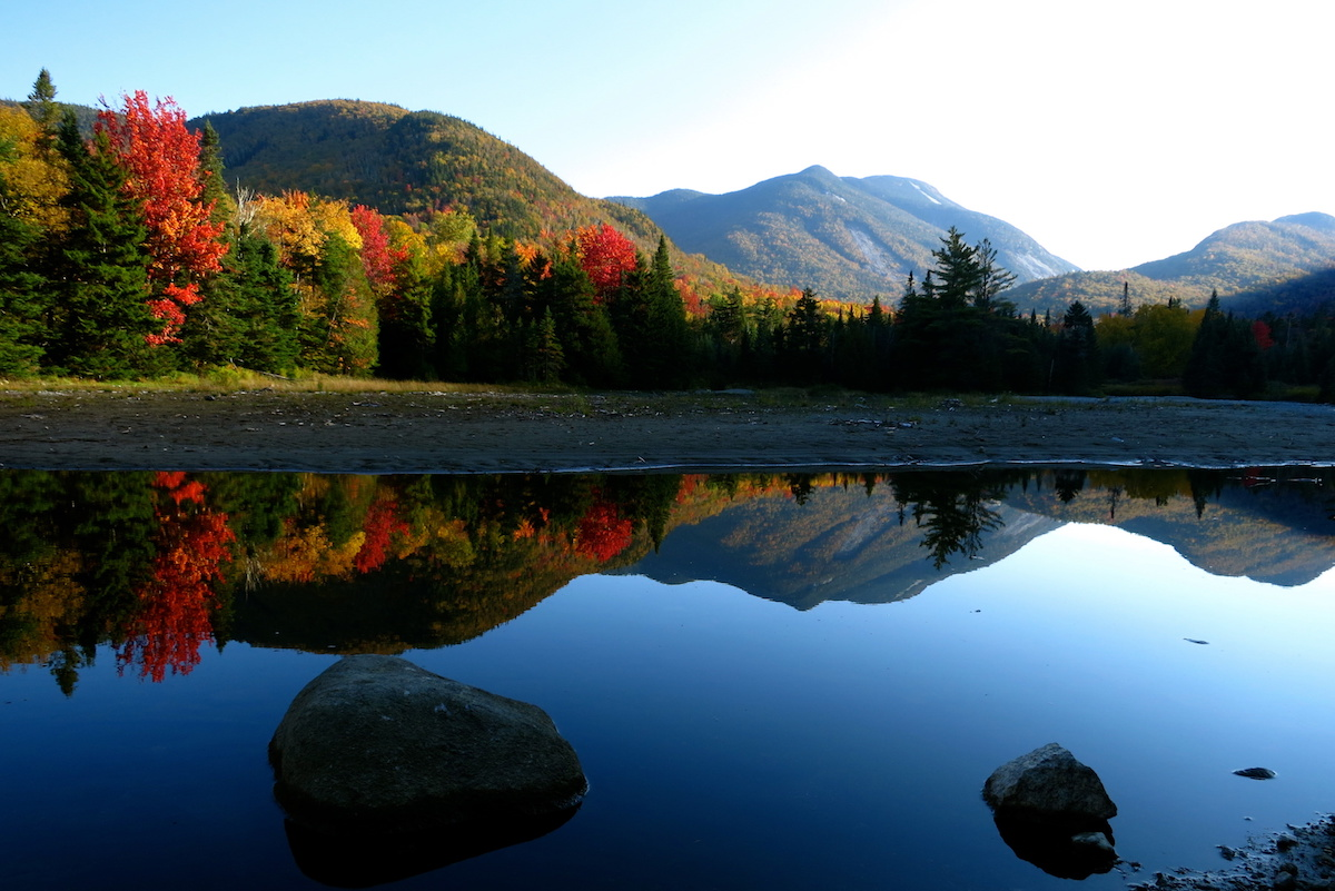 fall foliage in the Adirondacks reflected in a glassy mountain lake