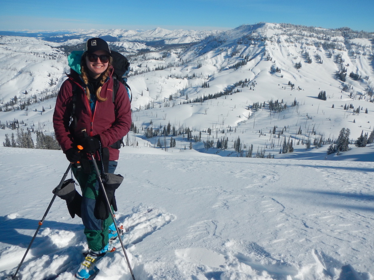 smiling NOLS student on backcountry skis in the Rockies on a sunny day