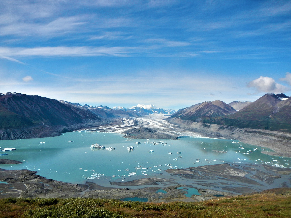 turquoise glacial lake as viewed from above with mountains surrounding