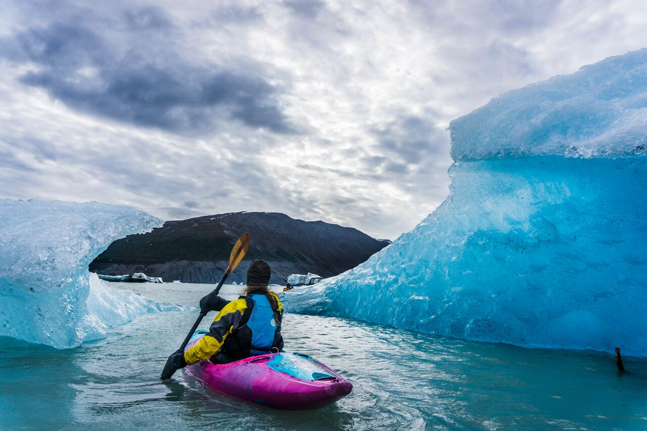 Woman in a pink kayak paddles between glacial ice