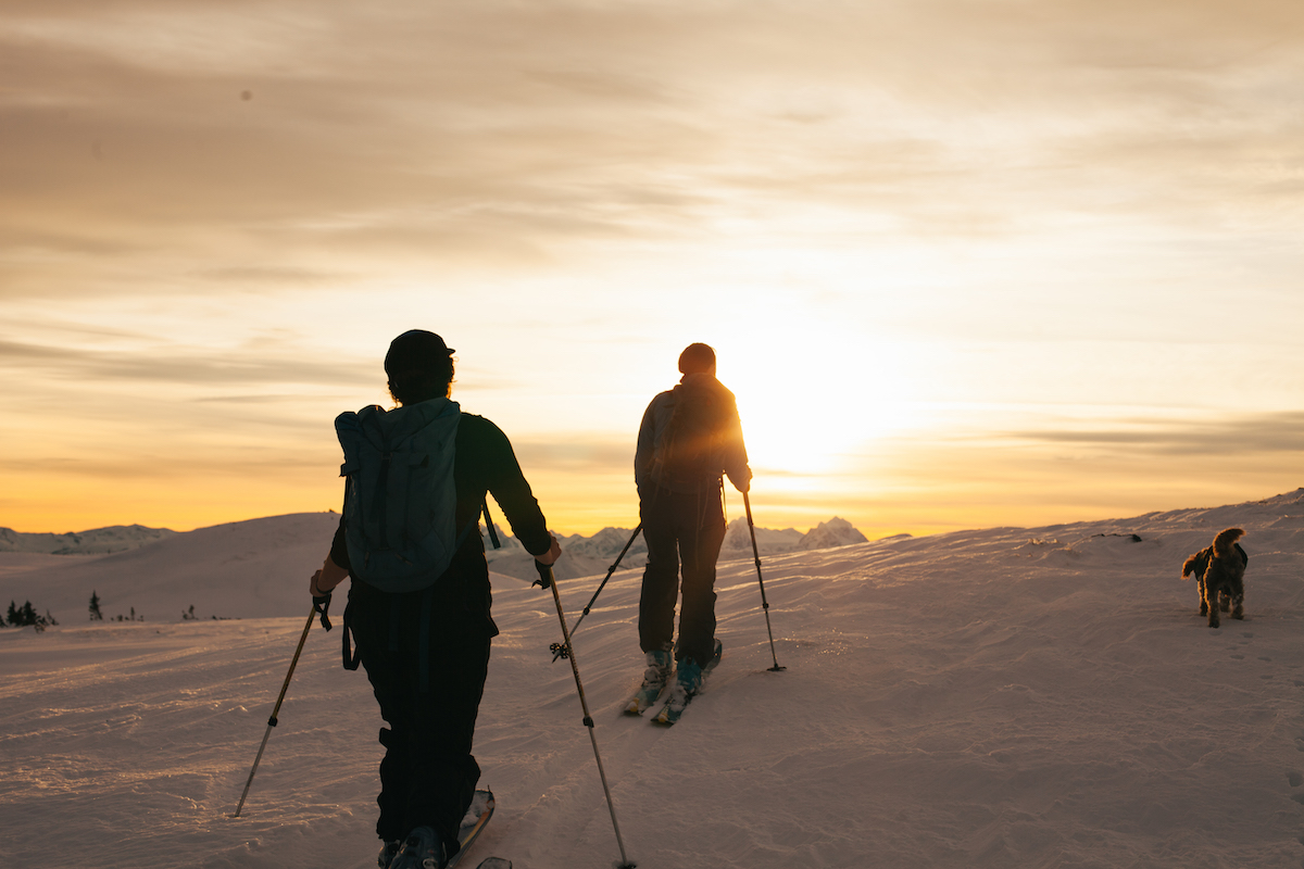 two silhouetted backcountry skiers reach the top of a snowy slope at sunset