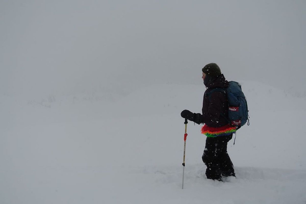 the author in a snowstorm standing on backcountry skis with a rainbow shirt sticking out from under her winter gear