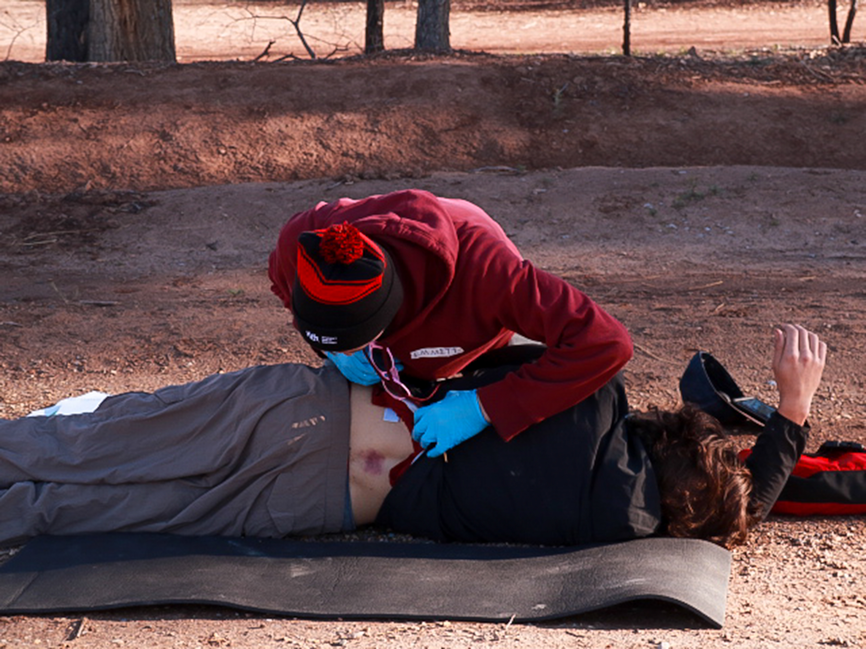 A rescuer log rolls a patient to check his bruised spine.