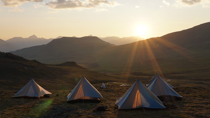 A group of four tents in a mountain meadow