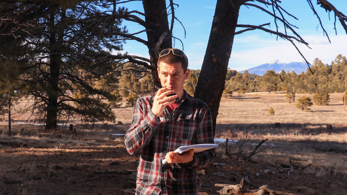 NOLS wilderness medicine student uses a radio to communicate a SOAP note in the outdoors