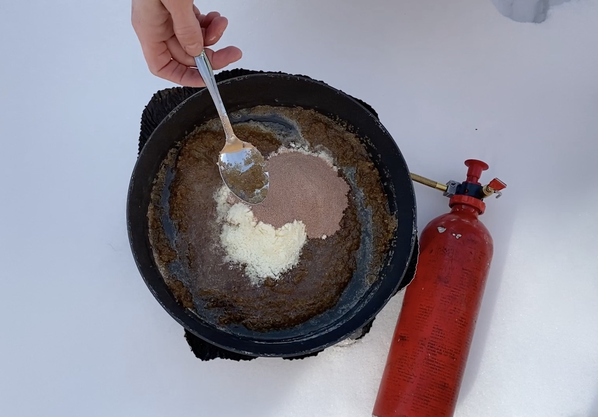 using a spoon to stir cocoa and powdered milk into no-bake cookie batter on a campstove