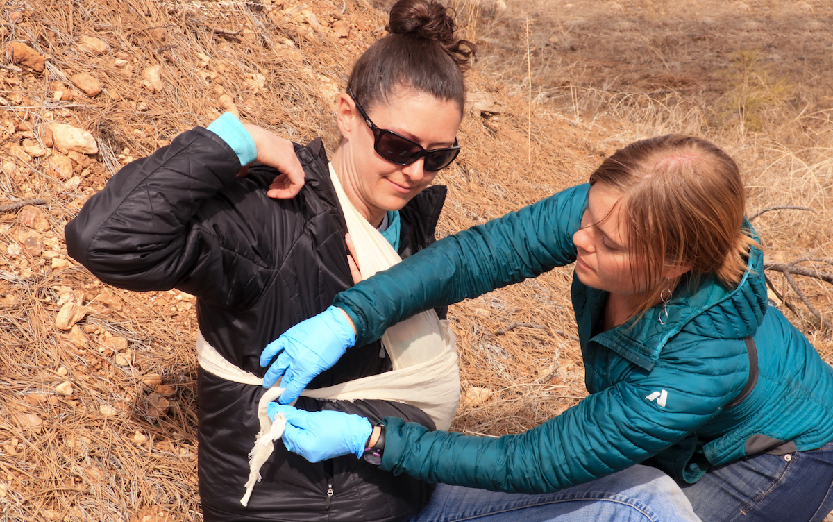 NOLS wilderness medicine student practices making an improvised sling and swath for a mock patient