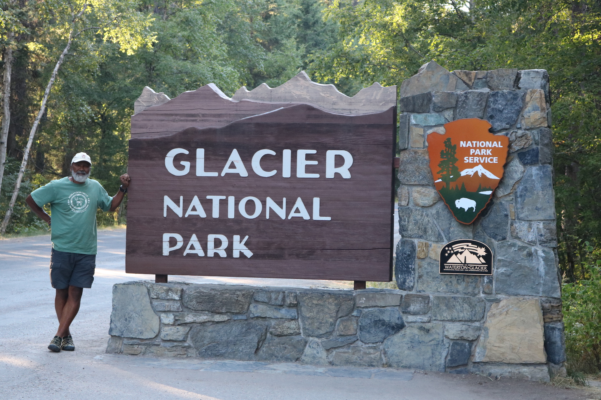 Carter McBride at the entrance sign to Glacier National Park