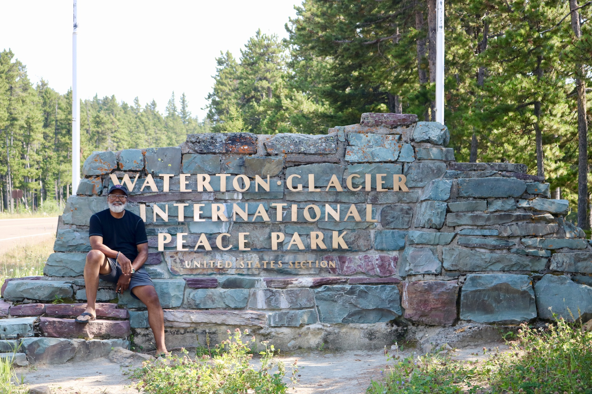 Carter McBride at the entrance sign to Waterton Glacier International Peace Park