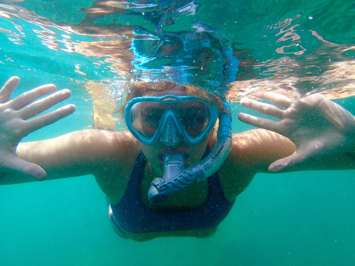 girl wearing purple top holds hands out while swimming underwater with a snorkel