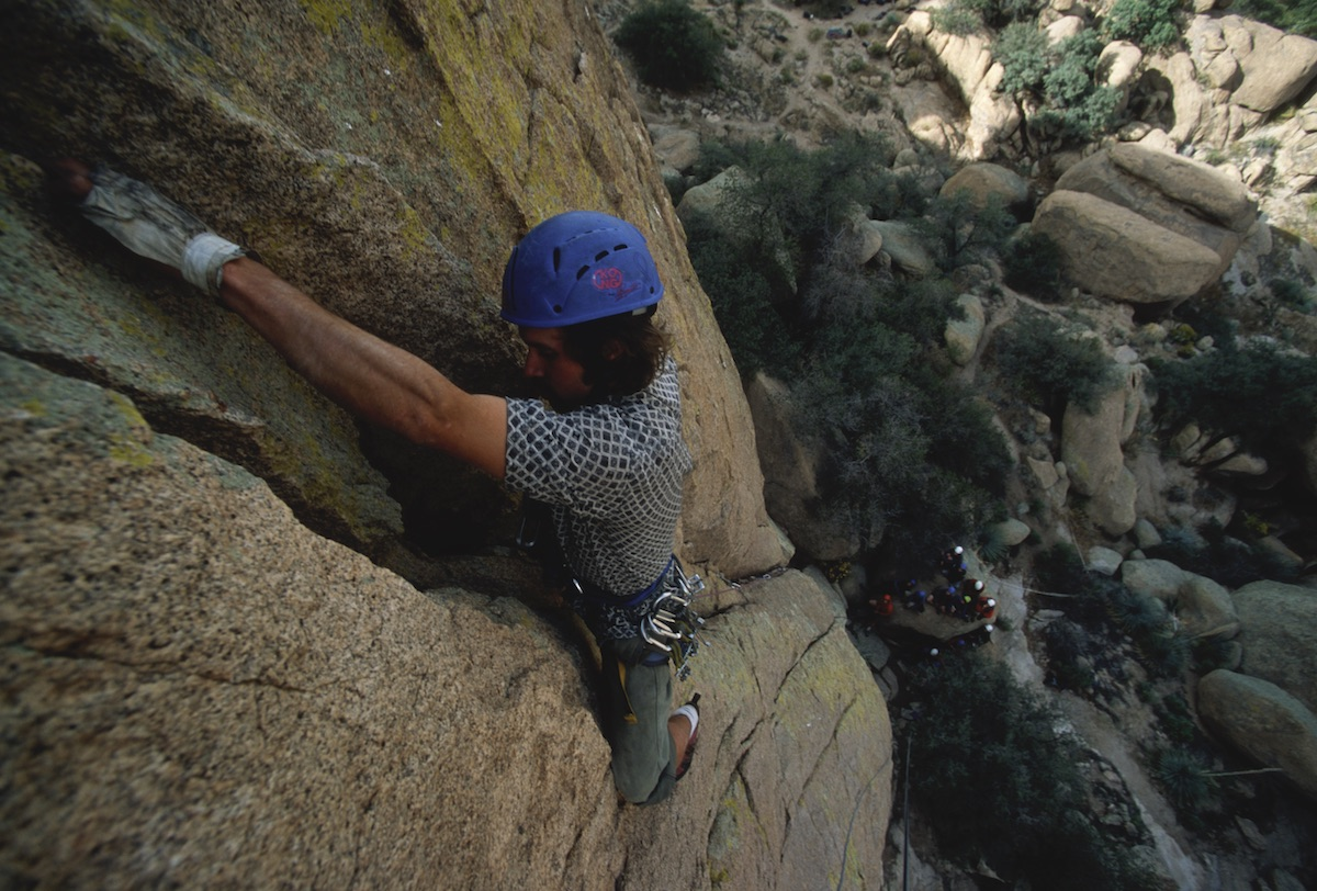 NOLS student wearing blue helmet rock climbs in the Southwest with cluster of teammates far below