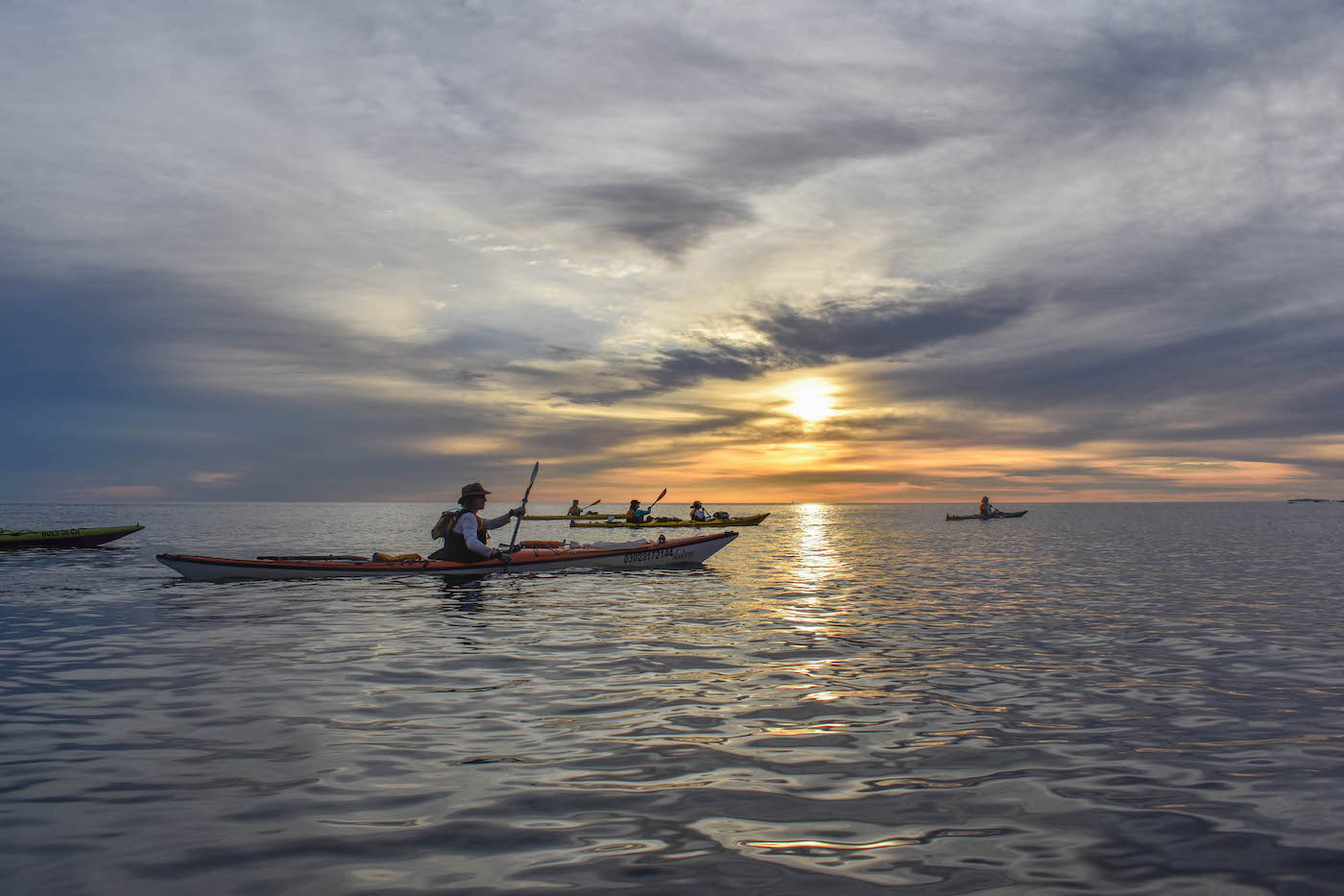 NOLS students paddle kayaks on silvery calm water with sun peeking through dark clouds