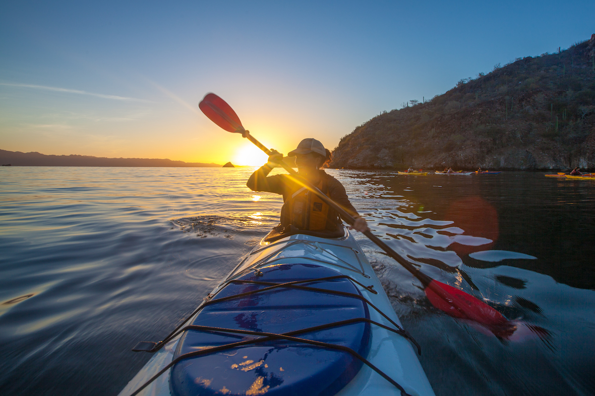 NOLS student paddles kayak in Baja with sun setting over calm water