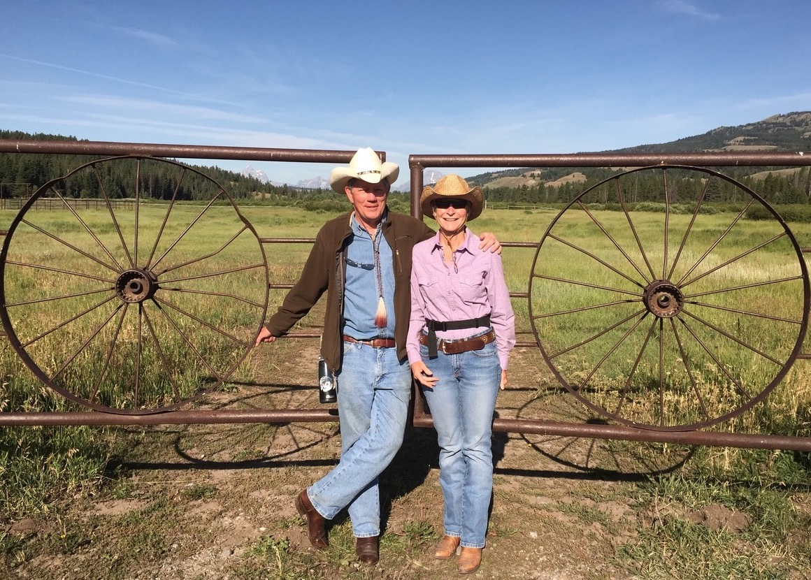 smiling couple wearing cowboy hats and boots stand in front of metal gate in Jackson, Wyoming
