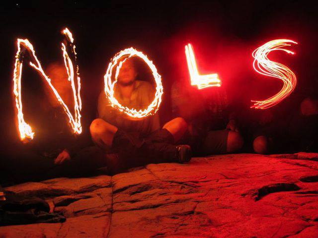 Four students sit on a rock in the dark and spell NOLS with glow sticks