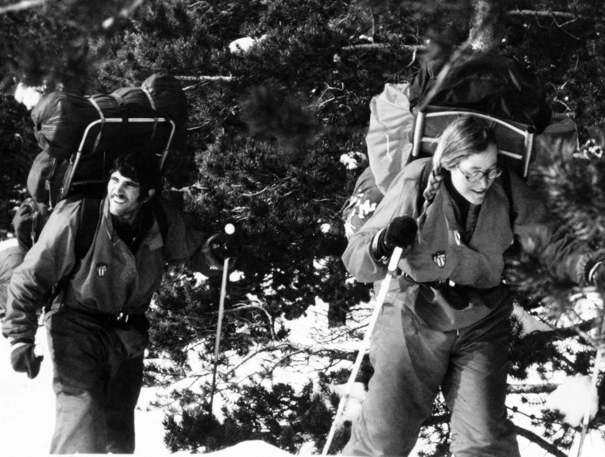black and white photo of smiling NOLS students hiking with huge frame packs in the 1970s