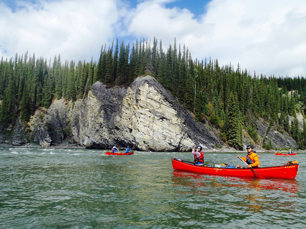 NOLS students paddle red canoes past rocky tree-lined coast in the Yukon