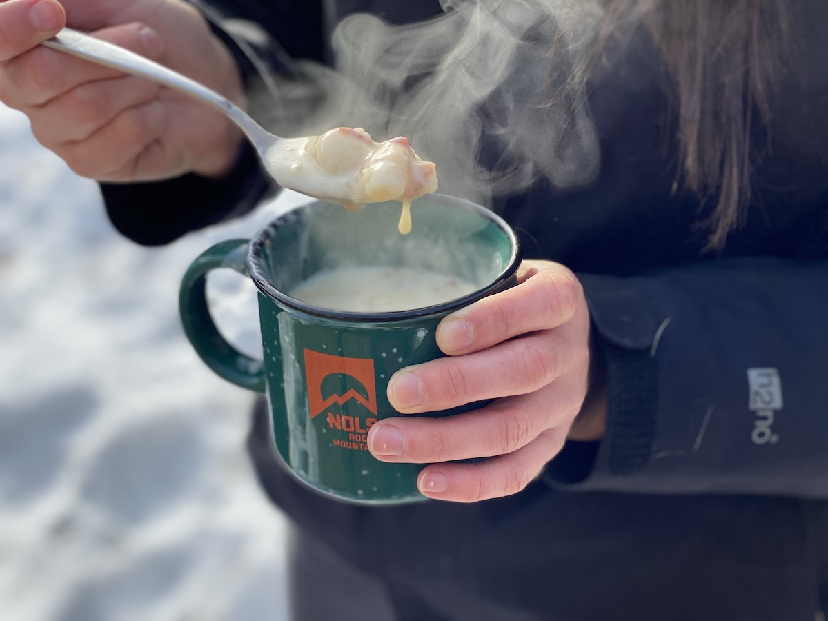 hands holding a steaming spoonful of cheesy potato soup in a green and orange NOLS mug