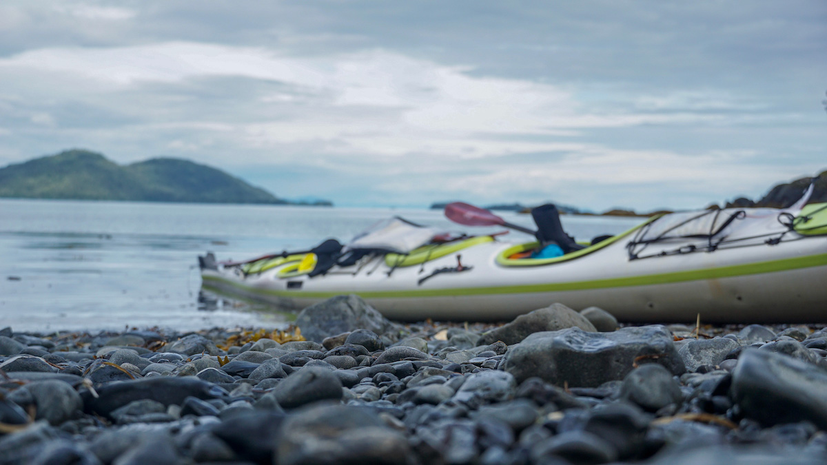 white and green sea kayak beached on a rocky shore in Alaska