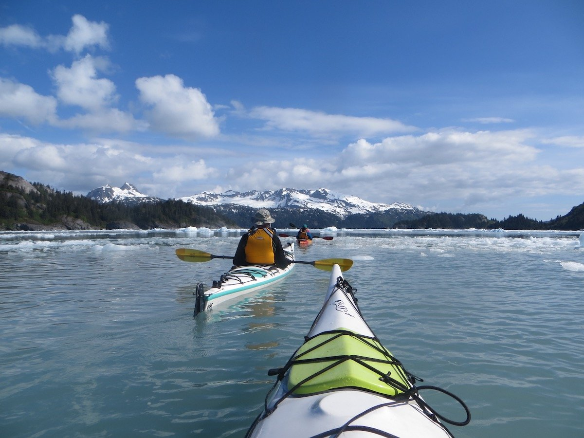 NOLS students sea kayaking in icy water with snow-capped mountains in the distance, as seen over the bow of a green and white kayak