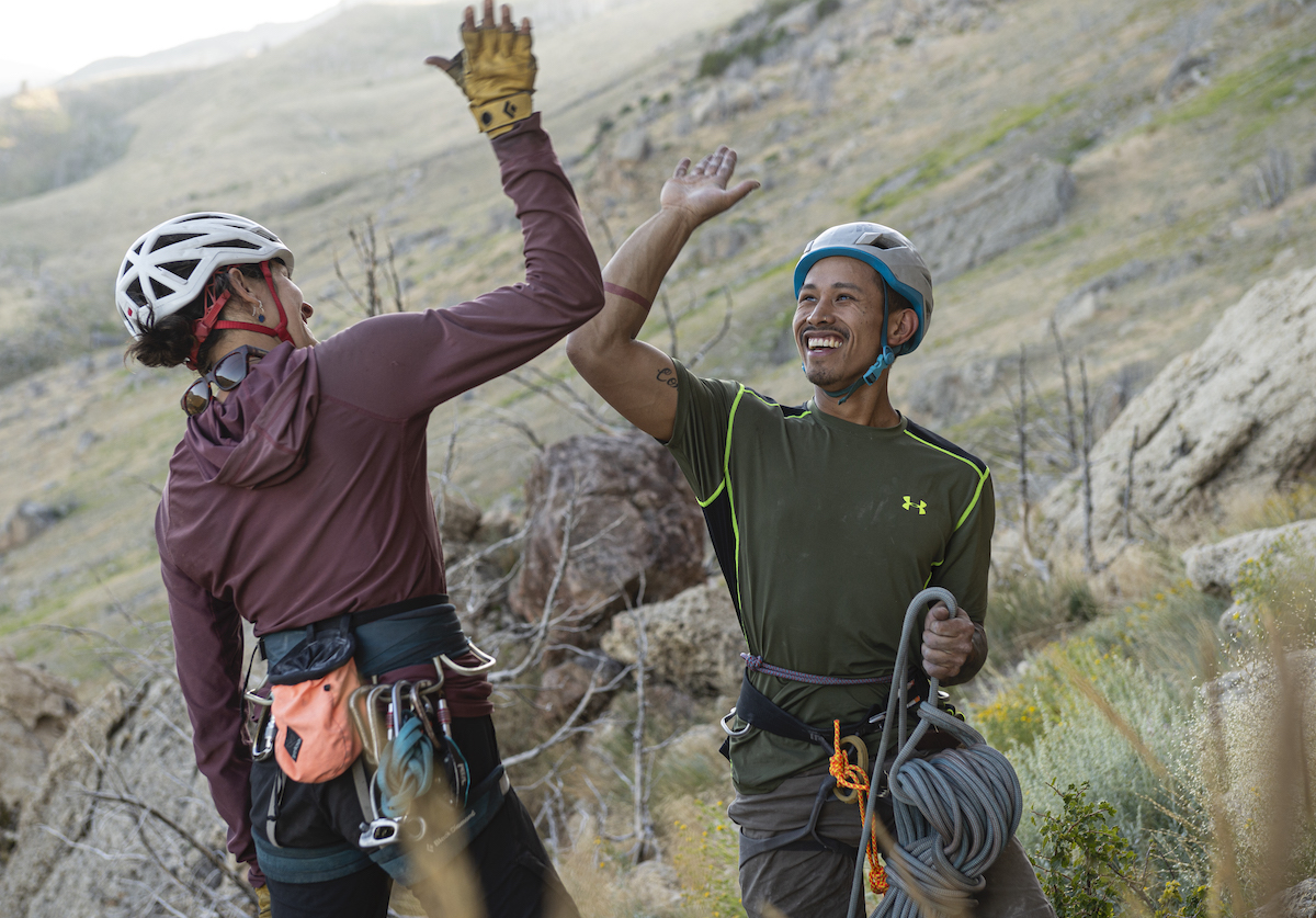 two smiling rock climbers high five