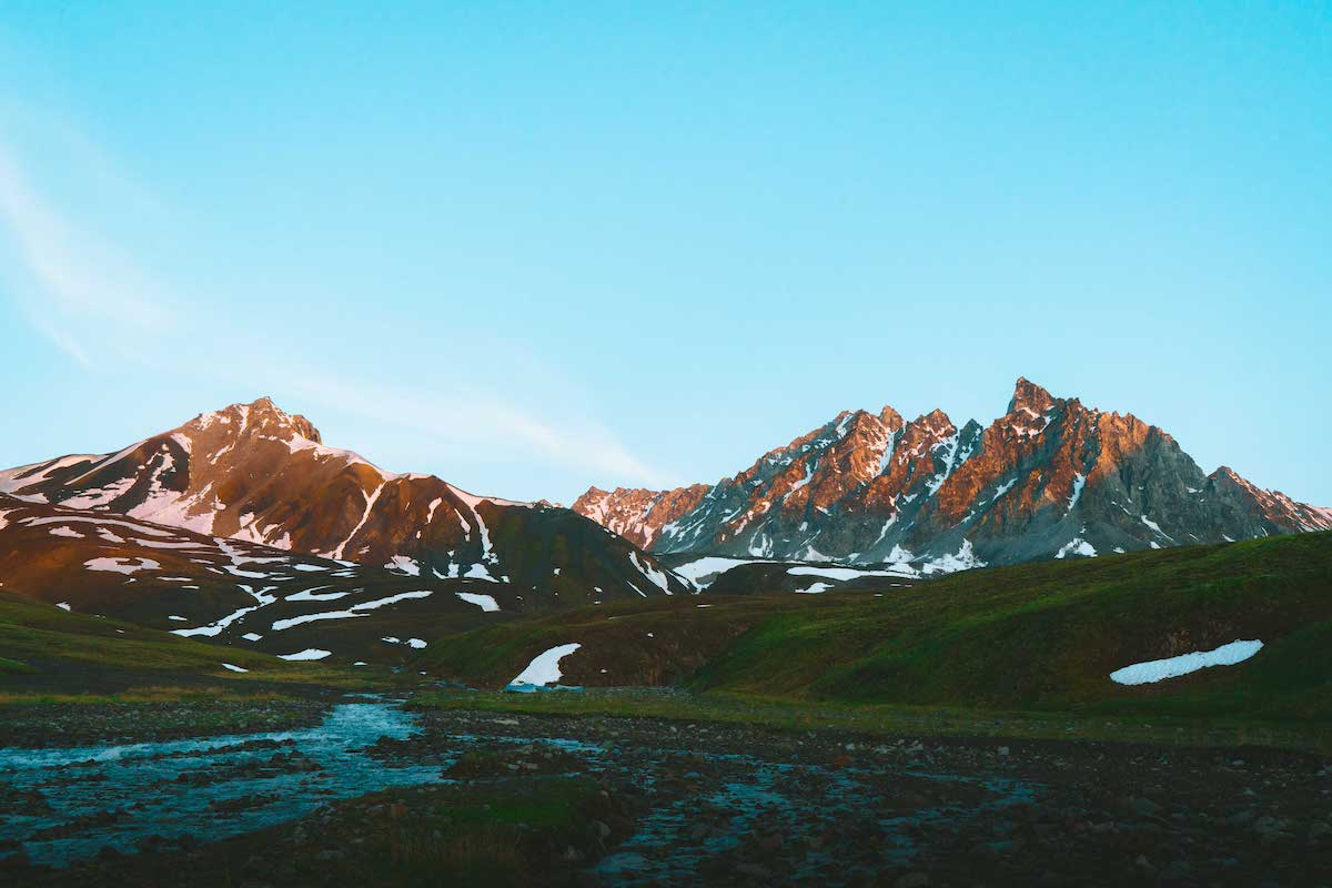 braided stream in a green valley in Alaska surrounded by rocky peaks with snow patches