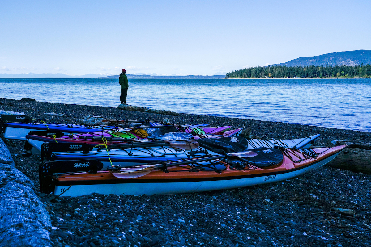 brightly colored sea kayaks on pebbly beach with lone figure gazing out at calm water